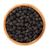 Aronia-Beeren, schwarze Trockenfrüchte in der hölzernen Schüssel lizenzfreie stockfotos