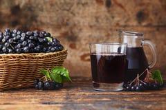 Aronia Berry Juice. Fresh aronia berries and aronia berry juice in glasses stock photo