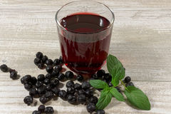 Aronia Berry Juice and mint on wooden table stock image