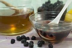 Aronia e miele in un piatto di vetro accanto ad un barattolo con miele Fotografia Stock Libera da Diritti