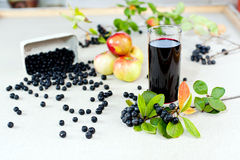 Aronia juice. Aronia - Black Choke berry fruits and juice. Separated pile of fruit, twig with leaves, and bunch Royalty Free Stock Photography