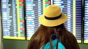 Aroport La fille avec de longs cheveux foncés avec un chapeau de paille vérifie l'embarquement de l'avion Femme regardant l'horai banque de vidéos