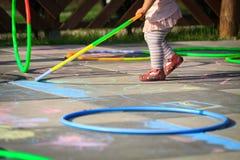 Aros pequenas do hula do jogo da menina no campo de jogos Imagem de Stock