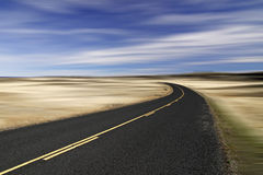 Around the Bend. A desolate road curving to the left into infinity Stock Photo