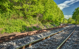 Around the Bend. Railroad tracks disappear around the bend on a sunny day Stock Photo