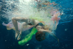 Around girls air bubbles under water. Royalty Free Stock Images