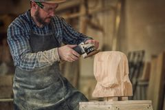 Сarpenter saw sculpture. Сarpenter, builder in work clothes saw to cut out sculpture from wooden a man`s head, using an angle grinder in the workshop, around a Royalty Free Stock Images