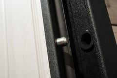 Arpenter instala una cerradura ladrón-resistente confiable en la puerta del metal foto de archivo