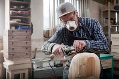 Сarpenter saw sculpture. Close up of a carpenter, builder in work clothes saw to cut out sculpture from wooden a man`s head  in the workshop, around a lot of Royalty Free Stock Photography