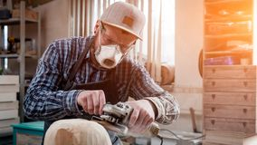 Сarpenter saw sculpture. Close up of a carpenter, builder in work clothes saw to cut out sculpture from wooden a man`s head in the workshop, around a lot of Stock Image