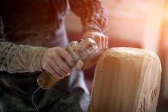 Сarpenter saw sculpture. Close up of a carpenter, builder in work clothes saw to cut out sculpture from wooden a man`s head, using an angle grinder in the Stock Photos