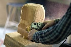 Сarpenter saw sculpture. Close up of a carpenter, builder in work clothes saw to cut out sculpture from wooden a man`s head, using an angle grinder  in the Stock Photography