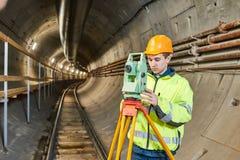 Arpenteur avec le niveau de théodolite aux travaux de construction de tunnel de chemin de fer au fond image stock