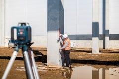 Arpenteur professionnel à l'aide du système et du théodolite de généralistes pour le niveau correct sur le chantier de constructi Photo stock