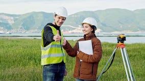 Arpenteurs masculins et féminins dans l'uniforme fonctionnant et casques souriant et montrant des pouces de signe, ce bon travail clips vidéos