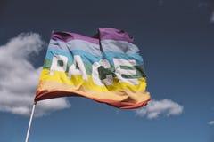 Arpentez, drapeau de paix ondulant contre le ciel bleu Photos stock