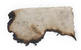 Arpillera quemada vieja en una superficie blanca Imagen de archivo libre de regalías