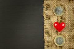 Arpillera vieja en un tablero de madera negro con las monedas euro válidas Fotografía de archivo libre de regalías
