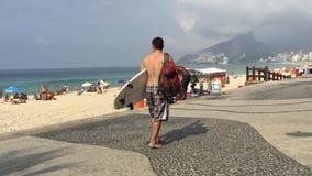 Arpoador Rio de Janeiro Brazil Morning. RIO DE JANEIRO, BRAZIL - JANUARY 16, 2015: Vendors and surfers share the boardwalk in a typical morning scene at Arpoador stock video footage