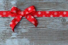 Arqueamiento rojo de la cinta de la Navidad en tarjeta de madera Foto de archivo libre de regalías