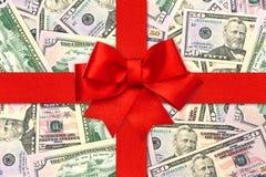 Arqueamiento rojo de la cinta del regalo sobre dólares americanos Foto de archivo libre de regalías