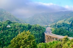 Arquee el puente a través de la garganta en las montañas de Apennine antes de la tempestad de truenos inminente imágenes de archivo libres de regalías