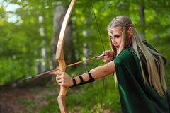 Arqueiro fêmea bonito do duende na caça da floresta com uma curva Imagens de Stock
