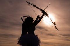 Arquero adolescente de la muchacha del ?ngel en puesta del sol Silueta de un cupido Vista lateral del arquero adolescente de la m imagenes de archivo
