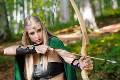 Arquero de sexo femenino hermoso del duende en la caza del bosque con un arco Imagen de archivo libre de regalías