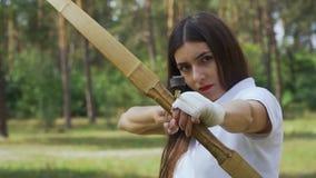 Arquero de sexo femenino que apunta su arco en blanco almacen de video