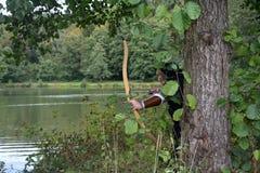 Arquero medieval con los soportes negros de la capilla ocultados detrás de árbol en el lago con la curva tensa foto de archivo