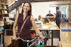 Arquitecto Arrives At Work en la bici que lo empuja a través de oficina Foto de archivo libre de regalías