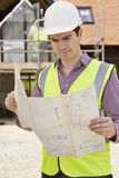 Arquitecto On Building Site que mira los planes para la casa Imagen de archivo