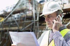 Arquitecto On Building Site que usa el teléfono móvil Imágenes de archivo libres de regalías