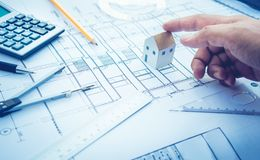 Arquitecto con el modelo de la pequeña casa a mano y el diseño de plan Concepto fotos de archivo libres de regalías