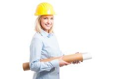 Arquitecto de la mujer que lleva el casco amarillo que sostiene modelos Imágenes de archivo libres de regalías