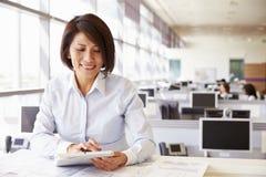Arquitecto de sexo femenino en el trabajo en una oficina usando la tableta foto de archivo libre de regalías