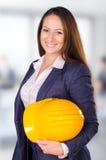 Arquitecto de sexo femenino joven que presenta con el casco Fotografía de archivo