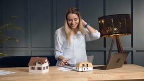 Arquitecto de sexo femenino joven que trabaja en nuevo desing de la casa usando modelo de la casa 3d almacen de metraje de vídeo