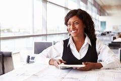 Arquitecto de sexo femenino joven que trabaja en su escritorio, mirando lejos Imagen de archivo