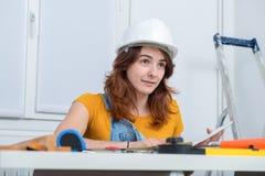 Arquitecto de sexo femenino sonriente de los jóvenes en la oficina fotografía de archivo