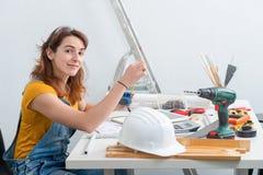 Arquitecto de sexo femenino sonriente de los jóvenes en oficina imágenes de archivo libres de regalías