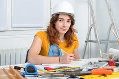 Arquitecto de sexo femenino sonriente de los jóvenes en oficina imagenes de archivo