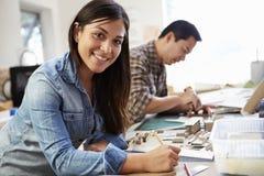 Arquitecto de sexo femenino Working On Model en oficina Imagen de archivo libre de regalías
