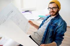 Arquitecto del inconformista que trabaja con planes de la construcción Foto de archivo