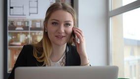 Arquitecto feliz de la mujer que habla por el teléfono móvil en la tabla en oficina creativa almacen de video