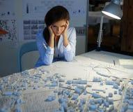 Arquitecto joven cansado que tiene un problema con sus disposiciones y modelos técnicos en un estudio del arquitecto Foto de archivo