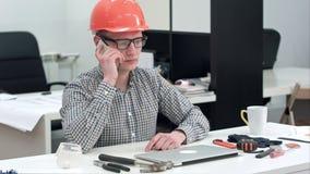Arquitecto joven en el casco que tiene llamada de teléfono importante almacen de metraje de vídeo