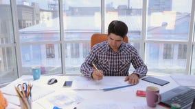 Arquitecto joven, hombre de negocios en la oficina limpia brillante moderna que trabaja con el modelo y planes almacen de video