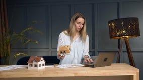 Arquitecto joven que trabaja con el modelo del modelo y de la casa usando el ordenador portátil almacen de metraje de vídeo